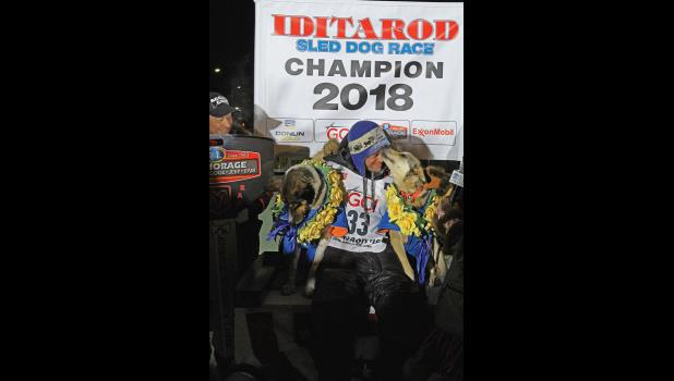 2018 CHAMPION— Joar Leifseth Ulsom of Norway won the Iditarod on March 14, 2018 at 3 a.m. At the champion podium he got a kiss from his lead dog Olive while holding his other lead dog Russeren.