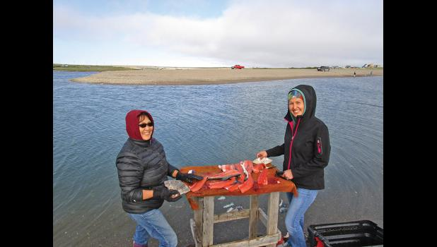 GONE FISHING— Marie Trigg and her niece Kellie Williams filet their catch at the mouth of the Nome River, on July 12.
