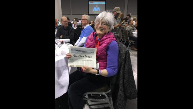 Nancy McGuire shows off a Nome Nugget newspaper during the 2016 Iditarod banquet In March in Anchorage.