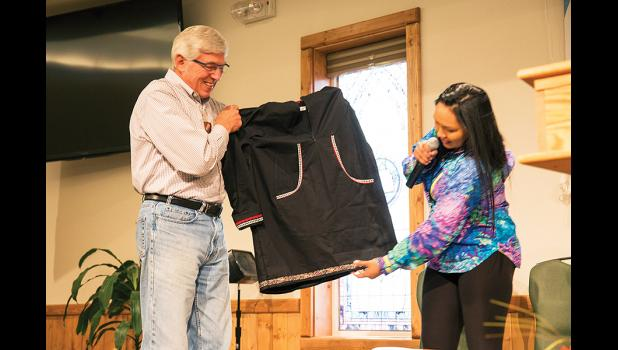 PRESENT— Lt. Governor Byron Mallott accepts the gift of a kuspuk from Kawerak's Hattie Keller after he delivered a speech opening the Leadership Conference in Nome, on Tuesday, Oct. 3
