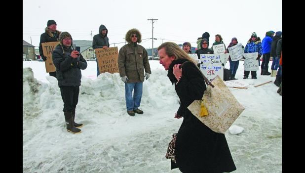 OMB Director Donna Arduin ducked as she hurried past protesters ouside Old St. Joe's after the Governor's AFP-sponsored roadshow in Nome.