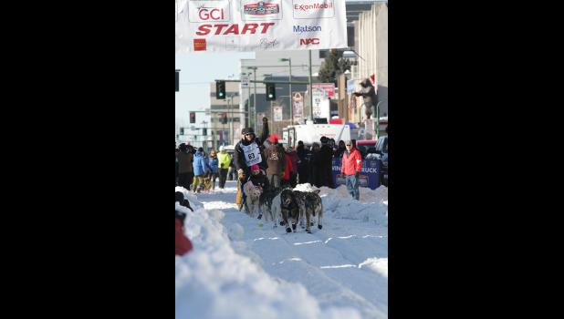 OFF THEY GO— Nome-grown musher Noah Burmeister gives the thumbs-up as he leaves the ceremonial start line at the 45th running of the Iditarod Trail Sled Dog Race on Saturday, March 4.