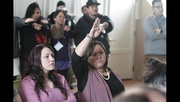 Melanie Bahnke raised her hand to be heard as members of the audience pointed to her in a gesture to appeal to Gov. Dunleavy to hear what Bahnke has to say.