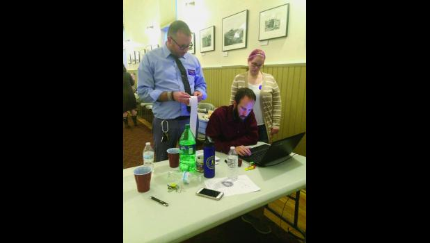 City Manager Tom Moran, City Clerk Bryant Hammond and Jill Nederhood work on tallying the unofficial election results on Tuesday, Oct. 4.