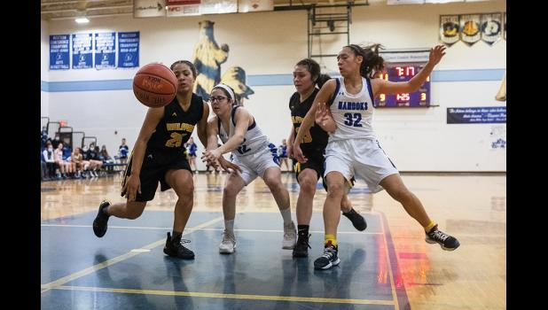 SCRAMBLE – Nome and Unalakleet players tussle for the ball Friday in the Nome-Beltz Middle High School gym. The players are, from left to right, Victoria Fisher, Claire Fry, Markayla Katchatag, and Natallie Tobuk.