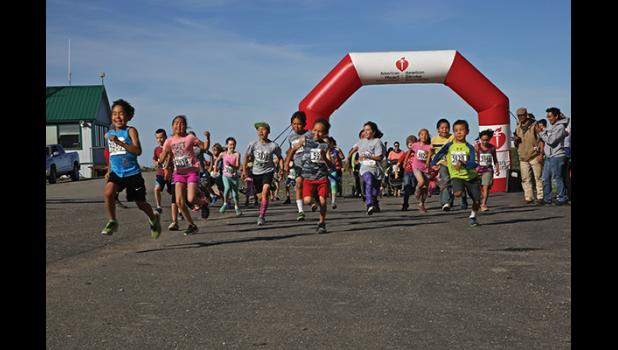 FULL BLAST— The youth division of last weekend's Fun Run in Unalakleet blasts out of the gates. The run was part of weekend geared towards healthy activities that included the annual Silver Salmon Derby, the Berry Bake-off and a community barbeque.